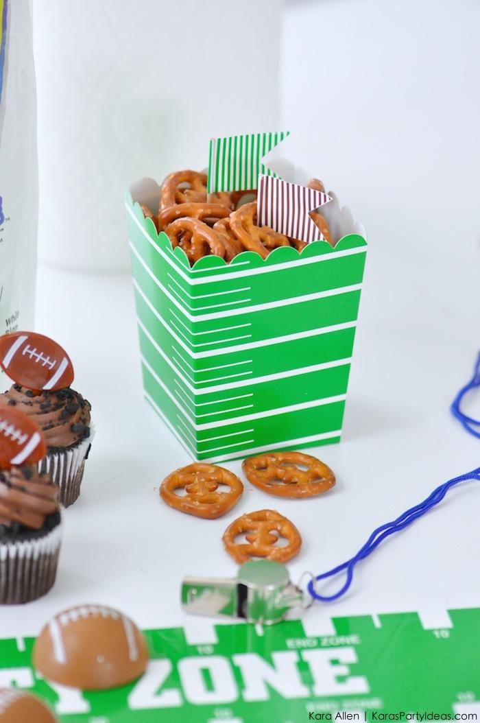 Portions can be placed inside themed containers, like these football field cups filled with pretzels.