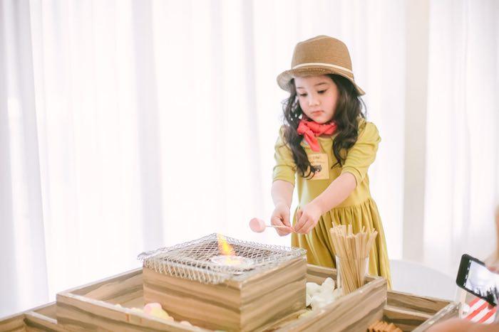 Little girl roasting a marshmallow from a Moonrise Kingdom Camping Birthday Party via Kara's Party Ideas | KarasPartyIdeas.com (9)