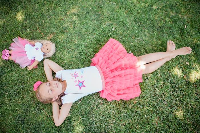 Birthday Girl + Doll Laying on the Grass at an American Girl Doll Inspired Birthday Party via Kara's Party Ideas | KarasPartyIdeas.com | The Place for All Things Party! (16)