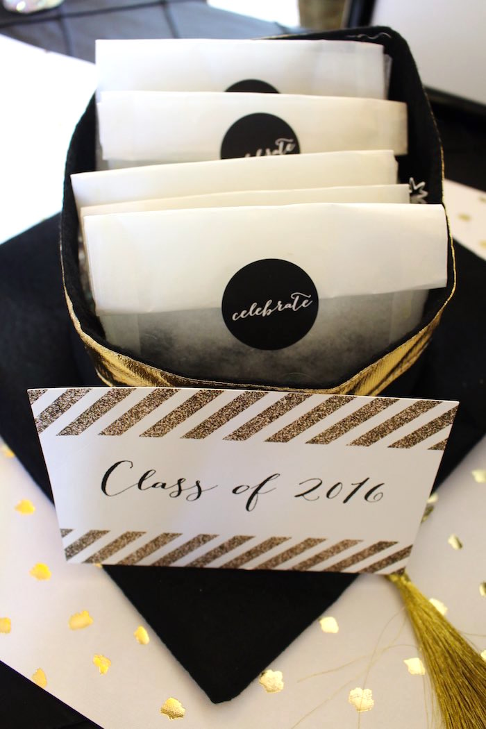 Party favor bags filled with black Sixlets candies, displayed in a black graduation hat from a Black, White + Gold Graduation Party via Kara's Party Ideas | KarasPartyIdeas.com (23)