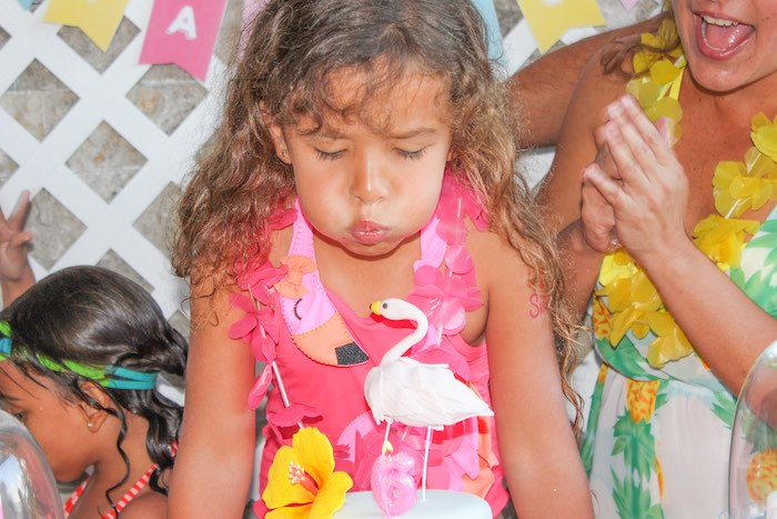 Birthday girl blowing out the candles on her cake from a Flamingo pineapple themed birthday party via Kara's Party Ideas | KarasPartyIdeas.com (9)