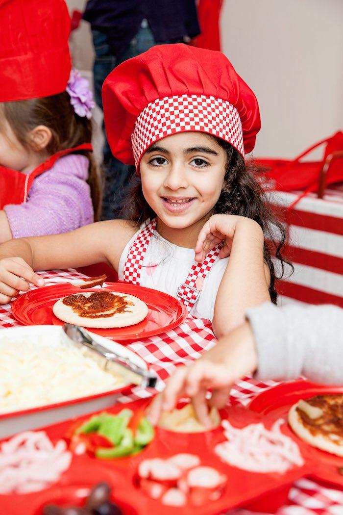 Birthday girl making a personal pizza from a Pizzeria Themed Birthday Party via Kara's Party Ideas KarasPartyIdeas.com (5)