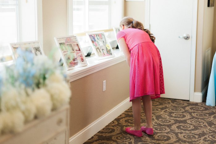 Girl looking at photo collages from a Vintage Garden 90th Birthday Party via Kara's Party Ideas KarasPartyIdeas.com (15)