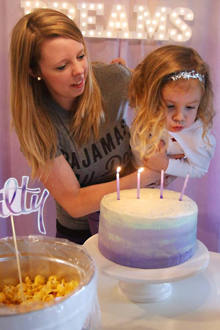 Blowing out the candles from a Popcorn & Pajamas Purple Movie Night via Kara's Party Ideas | KarasPartyIdeas.com (37)