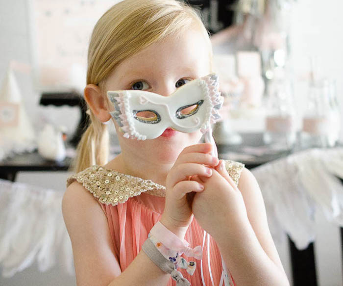 Little girl in disguise with her Masquerade Mask cookie at a Sweet Swan Themed Birthday Party via Kara's Party Ideas | KarasPartyIdeas.com (7)