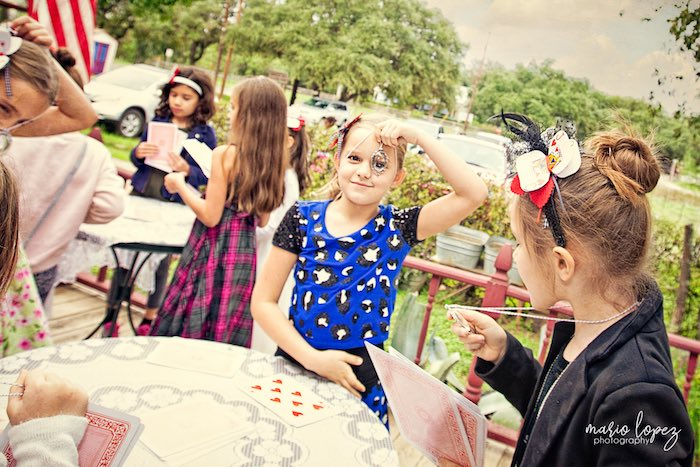Little girl looking through a looking glass from an Alice in Wonderland Birthday Party via Kara's Party Ideas | KarasPartyIdeas.com (32)