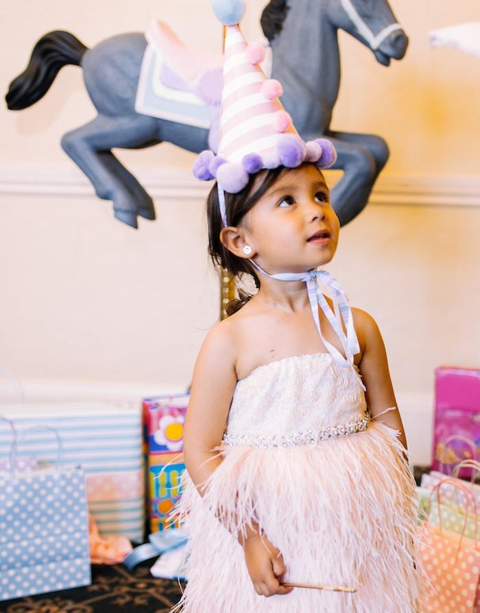 Pom pom party hat worn by the birthday girl at her Carousel of Dreams Birthday Party via Kara's Party Ideas | KarasPartyIdeas.com (14)