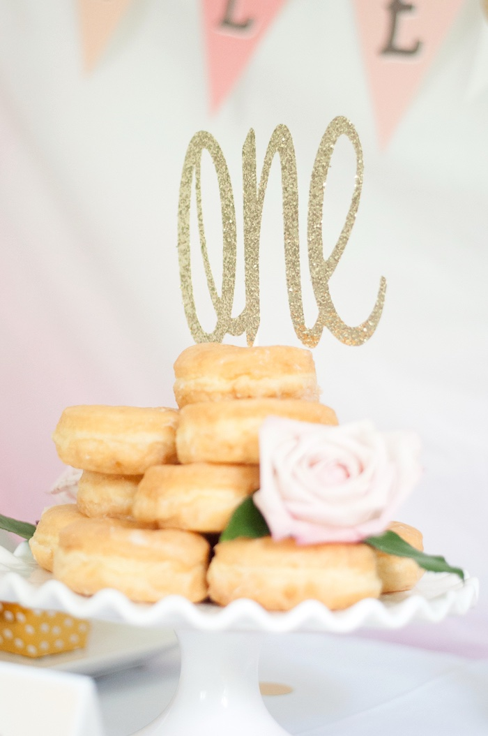 """Glazed donut stack with gold """"one"""" topper from a Gold + Glitter Our Little Pumpkin Birthday Party on Kara's Party Ideas 