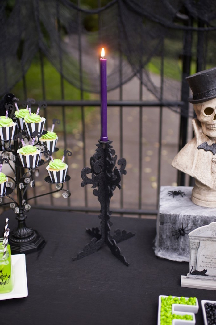 Lit purple candlestick with black candleabra from a Spooktacular Halloween Party via Kara's Party Ideas | KarasPartyIdeas.com (13)