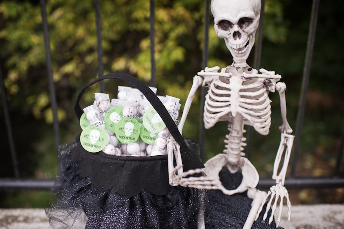 Plastic skeleton holding skeleton-inspired gumball tube party favors from a Spooktacular Halloween Party via Kara's Party Ideas | KarasPartyIdeas.com (37)