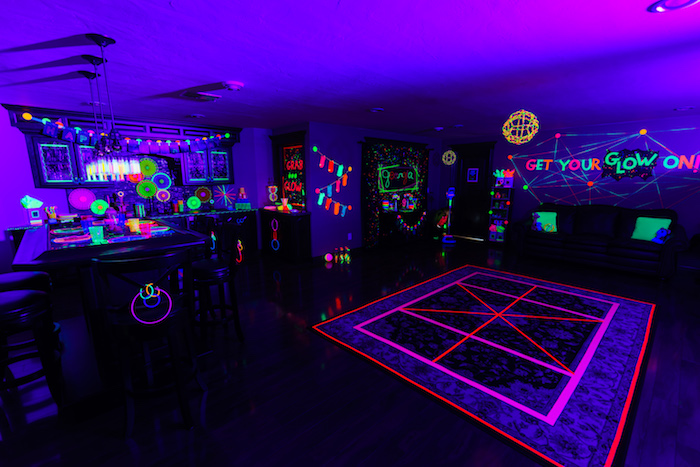 Add drama to your glow-in-the-dark party by mixing up your decorations. Place old-school burning candles in between blue neon bars. The effect will be magical.