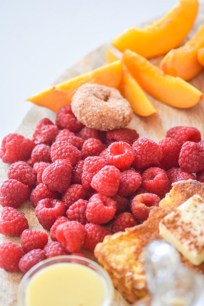Raspberries, peaches, and cinnamon swirl | French Toast Charcuterie Board with International Delight #AD via Kara's Party Ideas | karaspartyideas.com