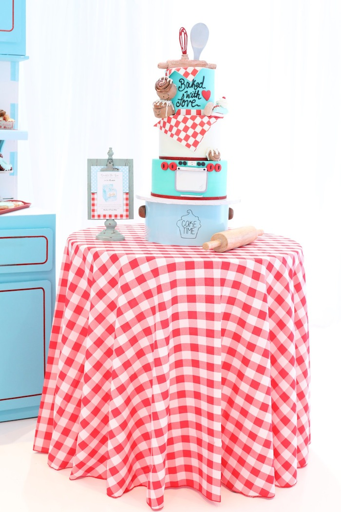 red checked table with cute bakery cake at bun in the oven twin baby shower via kara's party ideas karaspartyideas.com
