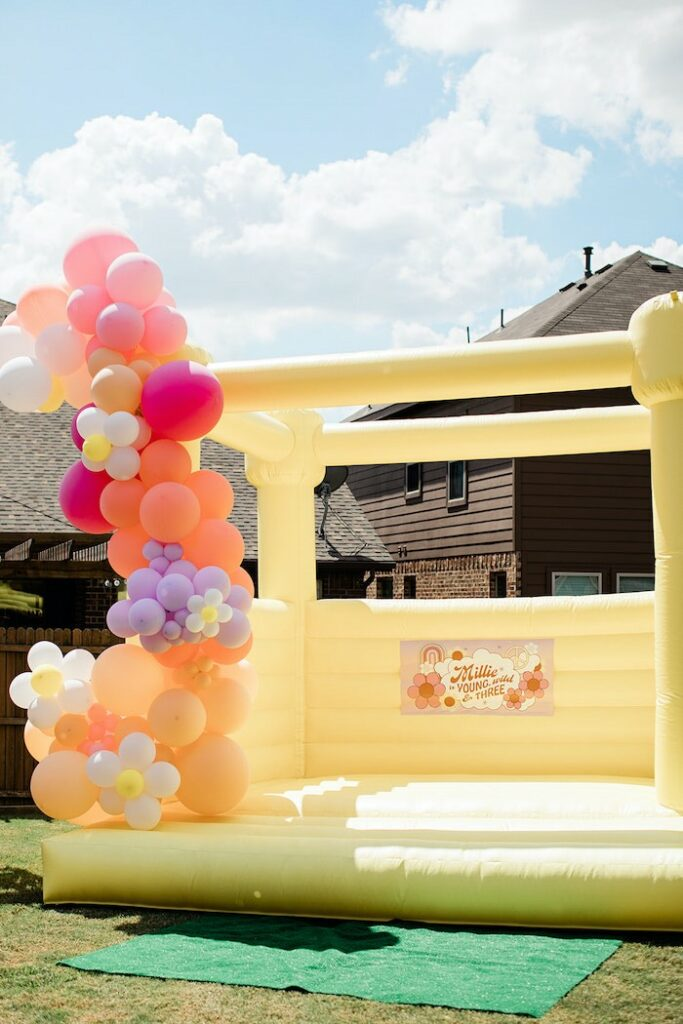 """Groovy Yellow Bounce House from a Groovy """"Young, Wild and THREE"""" Party on Kara's Party Ideas 